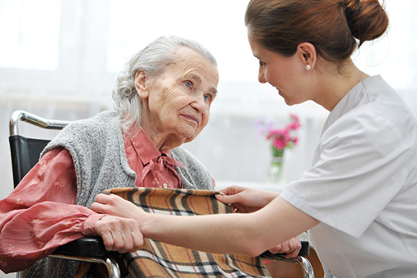 Nurse coving woman with blanket in nursing home