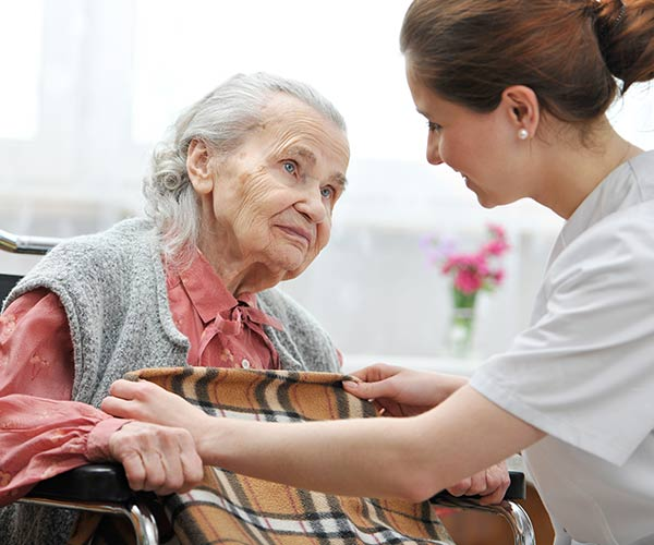 old woman looking at nurse covering with blanket to keep warm