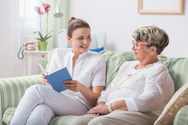 nurse reading to lady at WLC Firm